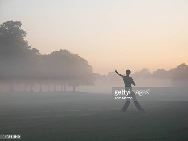 Woman practicing yoga in foggy field