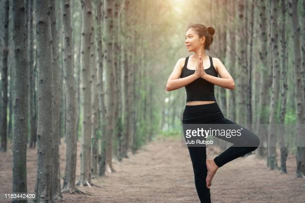 woman practicing yoga in fores - forens stock pictures, royalty-free photos & images