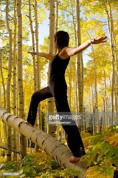 Woman practicing yoga in grove of aspen trees in Colorado