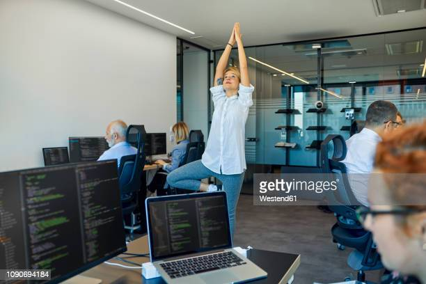 woman practicing yoga in office surrounded by busy colleagues - umgeben stock-fotos und bilder