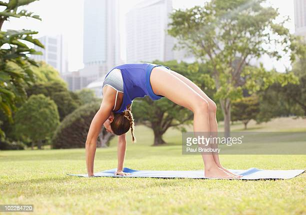 woman practicing yoga in park - bending over backwards stock photos and pictures