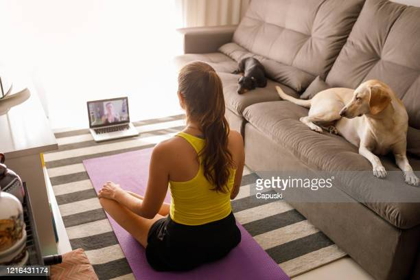woman practicing yoga in video conference - relaxation exercise stock pictures, royalty-free photos & images