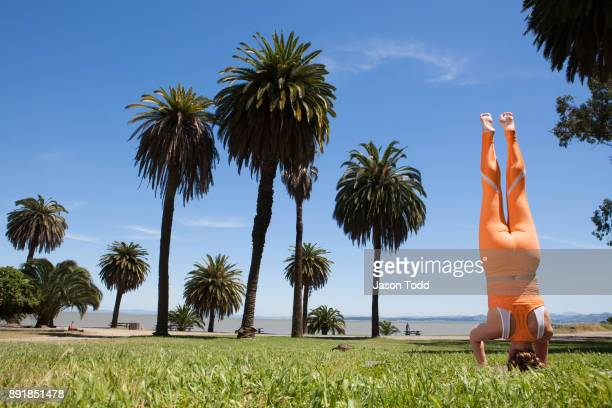 woman practicing yoga move Sirasana headstand outside in grass with palm trees and water
