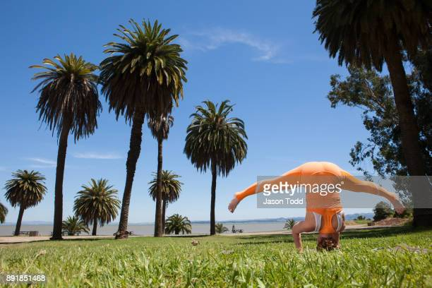 woman practicing yoga move Sirasana headstand with her legs open outside in grass with palm trees and water