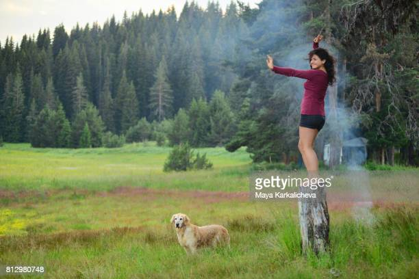 Woman practicing Yoga next to a Golden Retriever in a forest