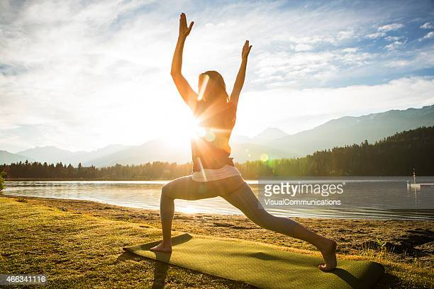 Woman practicing yoga next to a lake