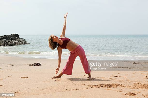 Woman practicing yoga on a beach