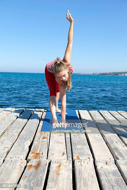 Woman practicing yoga on a boardwalk, bending over