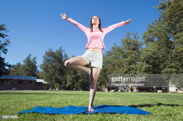 Woman practicing yoga on a mat outdoors