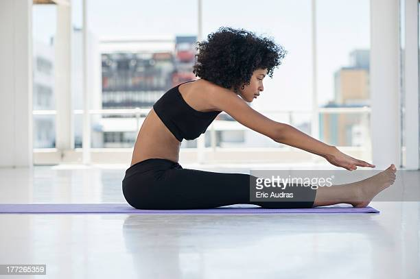 woman practicing yoga on an exercise mat - leggings stock pictures, royalty-free photos & images