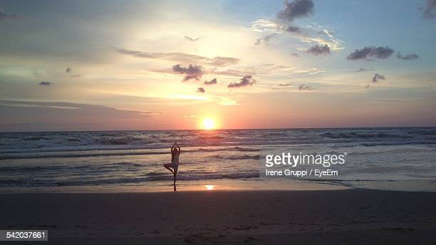 Woman Practicing Yoga On Beach Against Sky During Sunset
