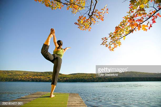 woman practicing yoga on dock, rear view, sunset - lake solitude (new hampshire) stock photos and pictures