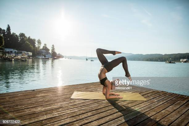 woman practicing yoga on jetty at a lake - yoga stockfoto's en -beelden