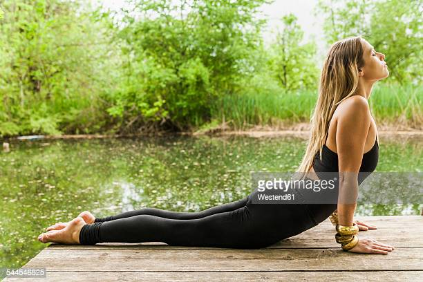 Woman practicing yoga on jetty