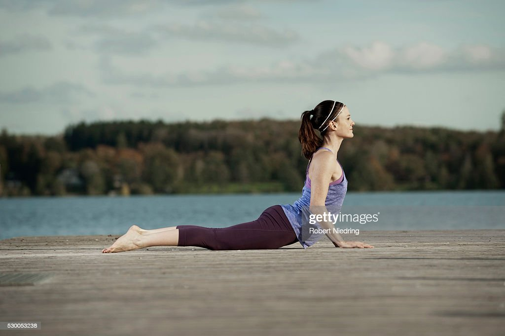 Woman practicing yoga on jetty, Woerthsee, Bavaria, Germany : Stock Photo