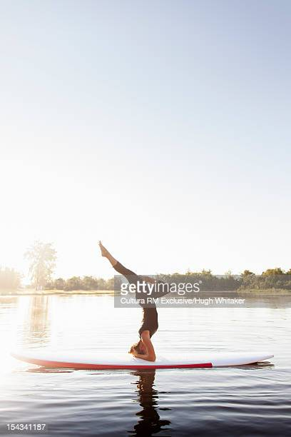 Woman practicing yoga on paddle board