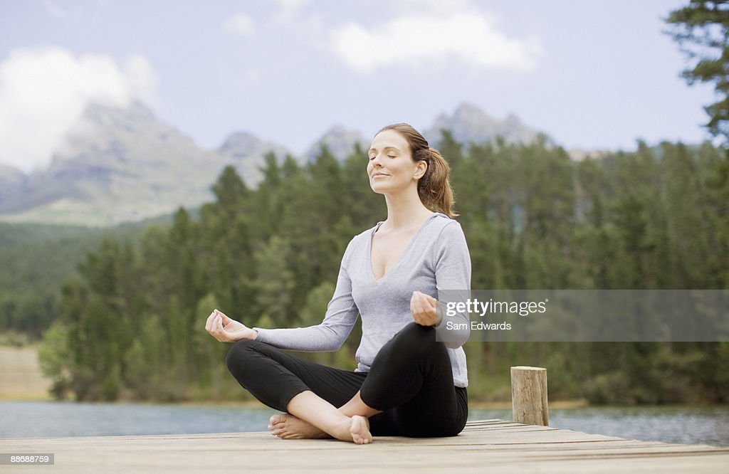 Woman practicing yoga on pier by lake : Stock Photo