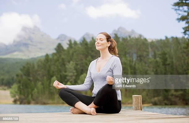 woman practicing yoga on pier by lake - mid adult women stock pictures, royalty-free photos & images