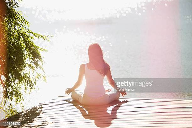 woman practicing yoga on pier - spirituality stockfoto's en -beelden