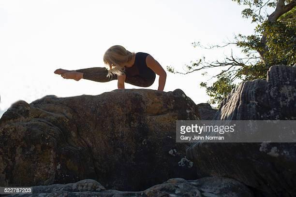 Woman practicing yoga on rocks.