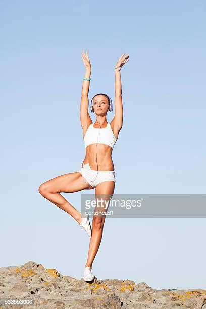 woman practicing yoga on rocks - wit hemd stockfoto's en -beelden