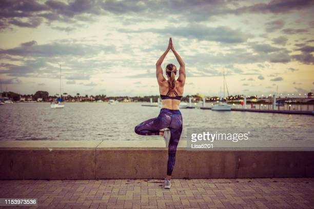 woman practicing yoga on the waterfront at dusk beautiful fit and healthy - lisa strain stock pictures, royalty-free photos & images