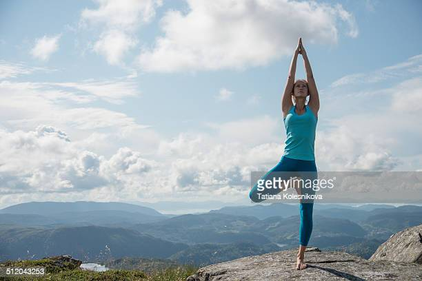 woman practicing yoga on top of a mountain - tree position stock photos and pictures