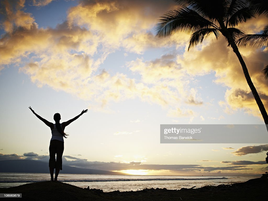 Woman practicing yoga on tropical beach at sunset : Stock Photo