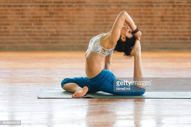 woman practicing yoga. one-legged king pigeon pose in side view. eka pada rajakapotasana - yogi stock photos and pictures