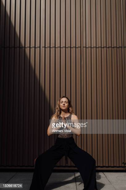 woman practicing yoga outdoors - one mid adult woman only stock pictures, royalty-free photos & images