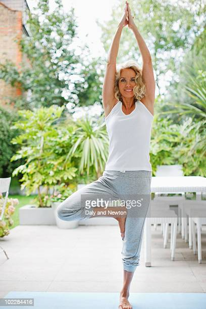 woman practicing yoga - tree position stock photos and pictures