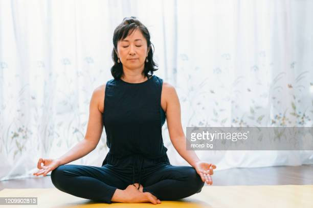 woman practicing yoga - curvy asian woman stock pictures, royalty-free photos & images