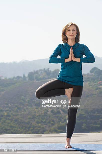 woman practicing yoga - standing on one leg stock pictures, royalty-free photos & images