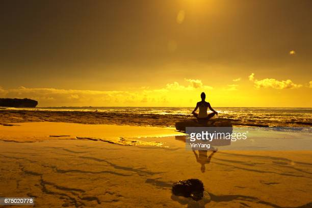 Woman Practicing Yoga Pose on the Beach at Sunset in Kauai, Hawaii