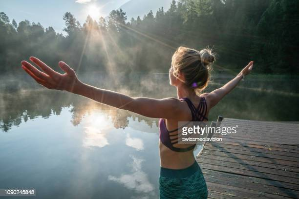 woman practicing yoga poses in nature, lake pier - body conscious stock pictures, royalty-free photos & images