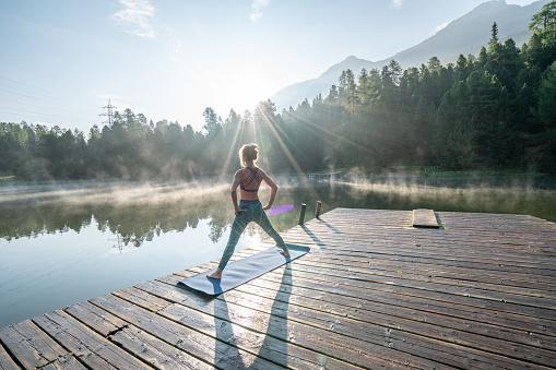 Woman practicing yoga poses in nature, lake pier 1090245986