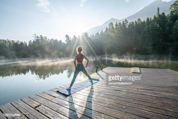 woman practicing yoga poses in nature, lake pier - yoga stock pictures, royalty-free photos & images
