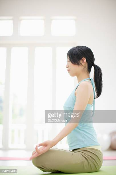 Woman practicing yoga, side view
