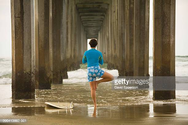 woman practicing yoga under pier with surfboard, rear view - la jolla stock pictures, royalty-free photos & images