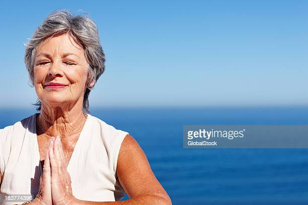 Woman practicing yoga with ocean in background