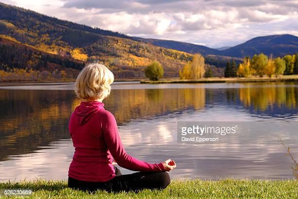 Woman practicing yoga/meditation by alpine lake