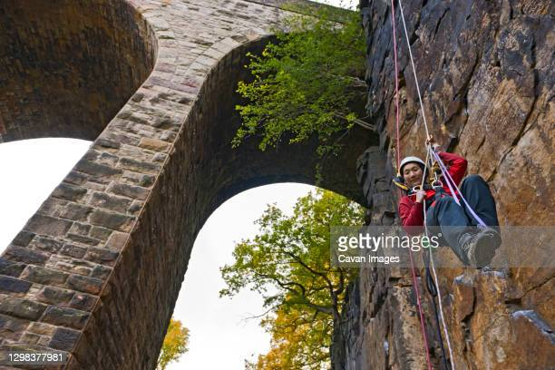 woman practising high rope access technique under viaduct in the uk - sheffield stock pictures, royalty-free photos & images