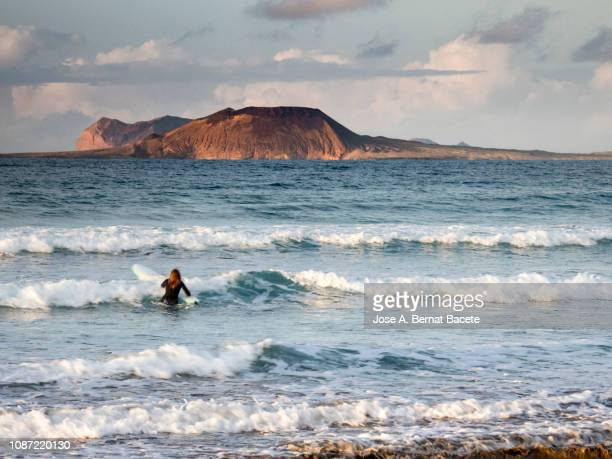 woman practising windsurfing in the beach in the sunset. lanzarote island, canary islands, spain. - lanzarote stock pictures, royalty-free photos & images
