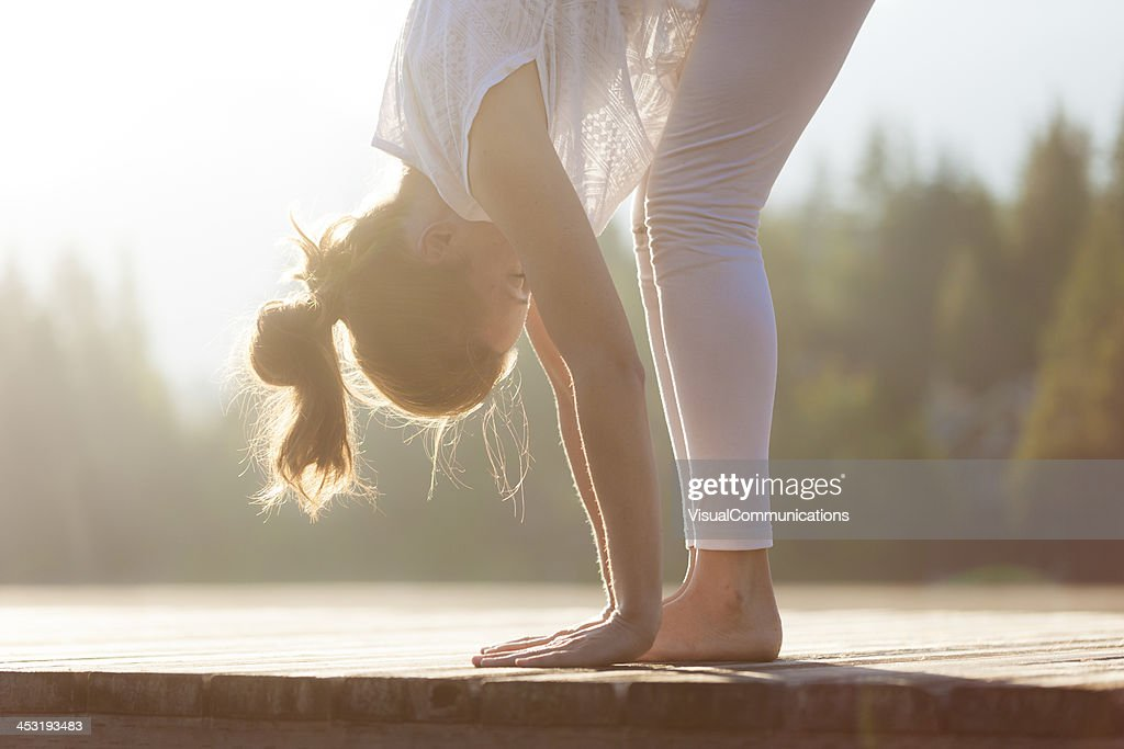 Woman practising yoga by the lake. : Stock Photo