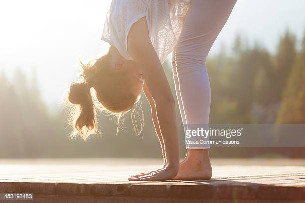Woman practising yoga by the lake.