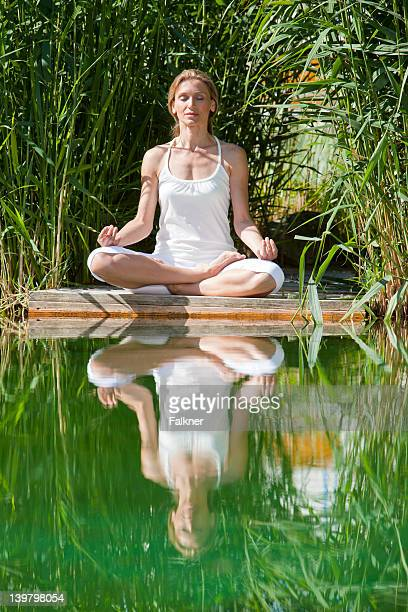 Woman practising yoga by the water