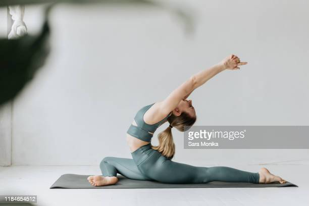 woman practising yoga in studio - yoga stock pictures, royalty-free photos & images