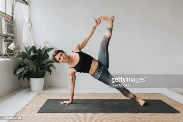 woman practising yoga in studio - yogi stock pictures, royalty-free photos & images
