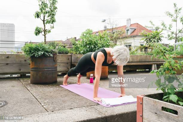 woman practising yoga on a roof terrace - plank position stock pictures, royalty-free photos & images