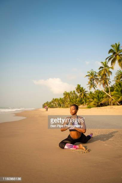 woman practising yoga on beach - ghana independence stock pictures, royalty-free photos & images